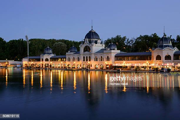 The popular Budapest Outdoor Ice Rink in the City Park aka Varosligeti Mujegpalya reflects at night in the boating lake While the enormous ice rink...