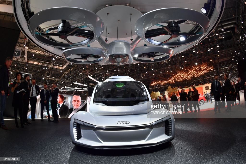 The 'Pop.up next' concept flying car, a hybrid vehicle that blends a self-driving car and passenger drone by Audi, italdesign and Airbus is seen during the first press day of the Geneva International Motor Show on March 6, 2018 in Geneva. The show opens to the public on March 8 and runs through March 18. / AFP PHOTO / Fabrice COFFRINI