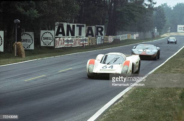 The Porsche 908 driven by Hans Herrmann and Gerard Larrousse leads the Ford GT40 of Jacky Icks and Jackie Oliver on the approach to Arnage during the...