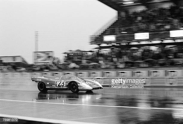 The Porsche 917K of Richard Attwood and Hans Hermann passes the pits in a sheet of spray on the way to winning the Le Mans 24 Hours race Le Mans June...
