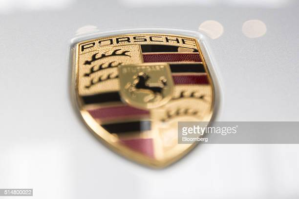 The Porsche badge sits on a Porsche Cayenne GTS luxury automobile on display inside a Porsche AG showroom in Stuttgart Germany on Friday March 11...