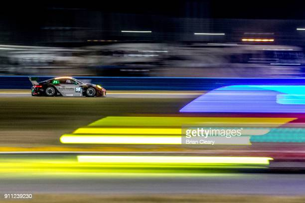 The Porsche of Patrick Long Christina Nielsen of Denmark Robert Renauer of Germanyand Mathieu Jaminet of France races on the track at night during...
