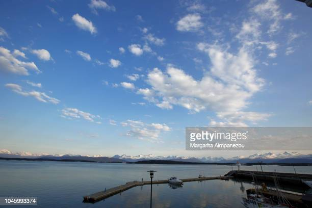 The port of Molde with one sole boat and the clouds reflecting on the water