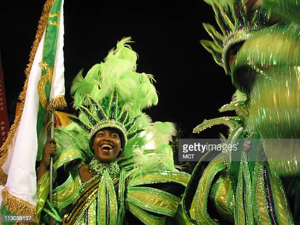 The portabandeira or flag bearer smiles as the Imperio Serrano samba school makes its way down the Carnaval parade route in the early morning hours...