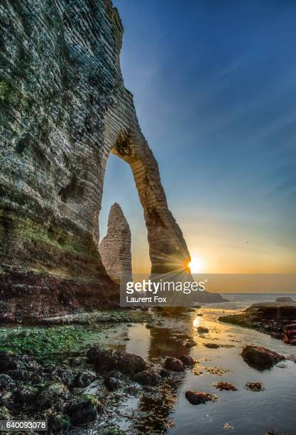 The Porte D'Aval rock formation in Etretat, France during the sunset.
