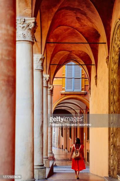 the porticoes of bologna and tourist with orange dress. emilia romagna, italy - iacomino italy foto e immagini stock