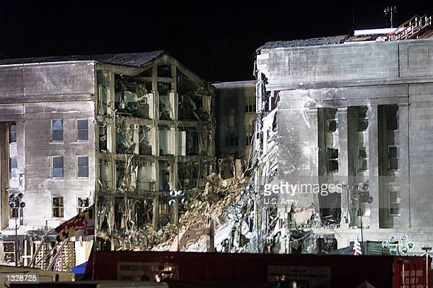The portion of the Pentagon that was hit by a hijacked airplane September 11 2001 is lit up by artificial light as roundtheclock recovery efforts...