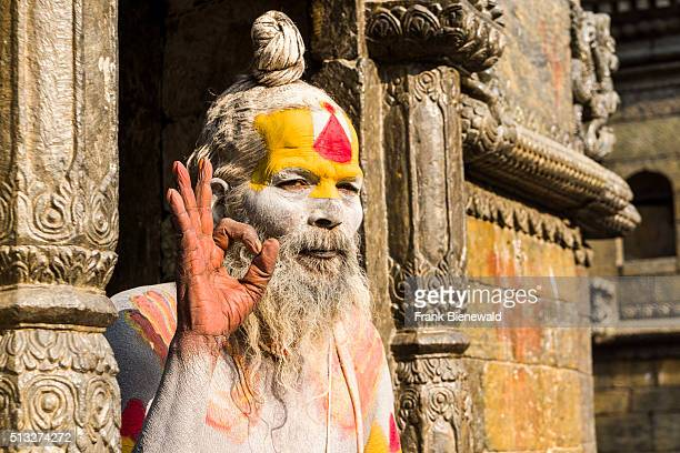 The portrait of a naked Sadhu holy man sitting in a doorway of Pashupatinath Temple