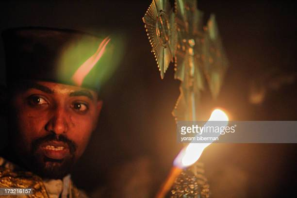 The portrait of a priest holding a cross and a candle, at a dark place. The photo was taken at the Light Saturday feast , at the Ethiopian compound...