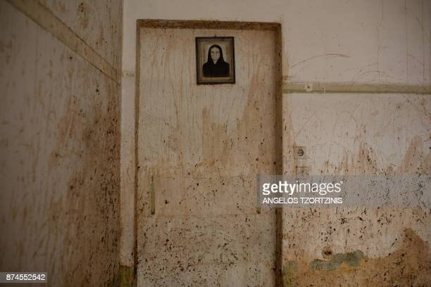 The portrait of a woman hangs on a wall splattered with floodwater and mud in the town of Mandra northwest of Athens on November 15 after heavy...