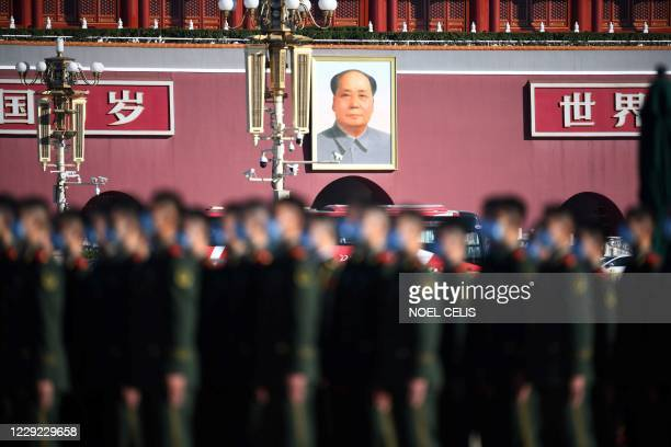 The portrait of late communist leader Mao Zedong is seen behind paramilitary police officers as they gather in Beijing's Tiananmen Square ahead of a...