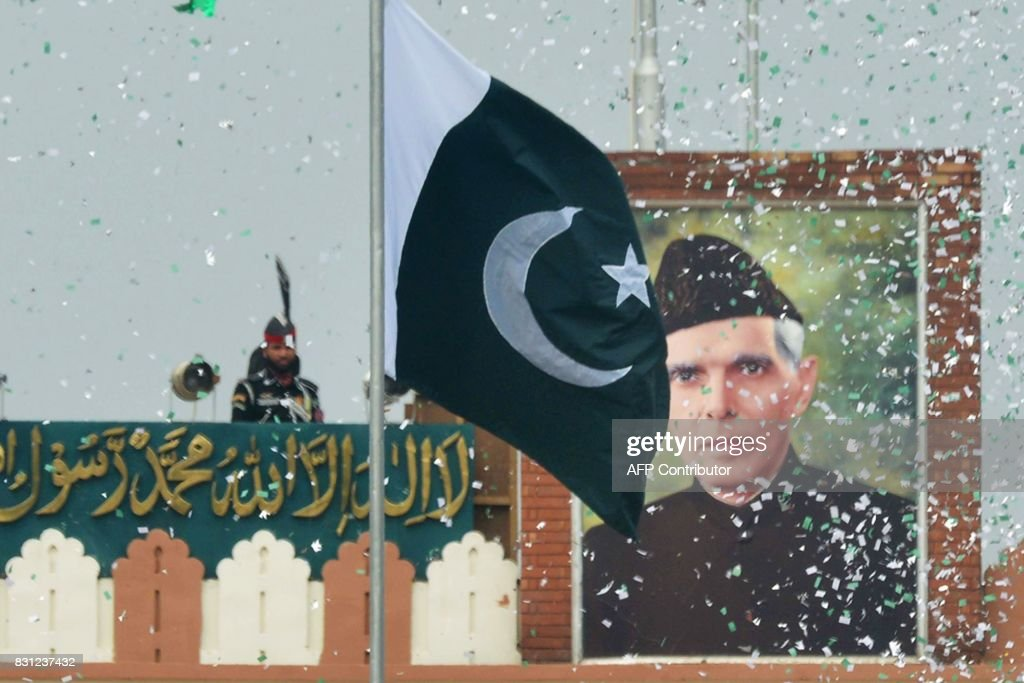 The portrait of Muhammad Ali Jinnah is seen at at the IndiaPakistan Wagah border post as a Pakistani Ranger unfurls the Pakistani national flag...