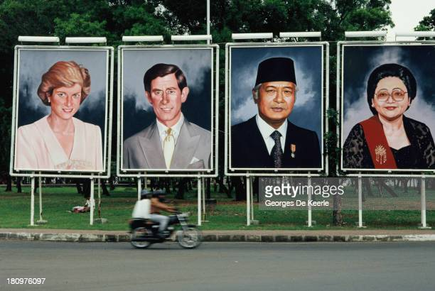 The portraits of Diana Princess of Wales Charles Prince of Wales President Suharto of Indonesia and First Lady Siti Hartinah are seen by a roadside...