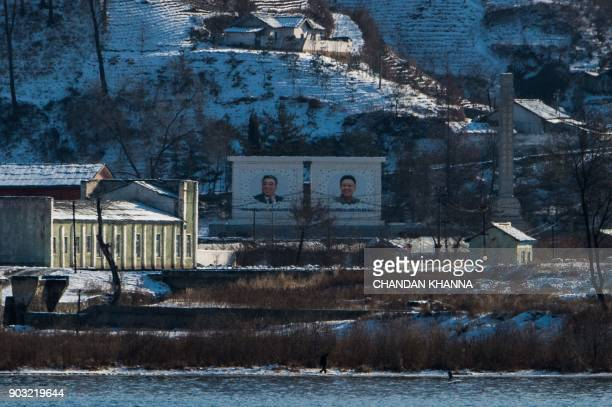 The portraits of late North Korean leaders Kim IlSung and Kim JongIl are seen in North Korea's Sakchu county in North Pyongan province as seen from...