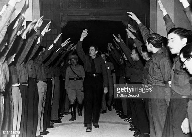 The Portugese fascist party the National Sydicalists known as the Blue Shirts salute their leader Senor Rolao Preto in a style similar to that used...