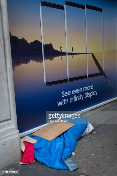 The possessions of a homeless person beneath an aspirational ad for Samsung's Infinity Display and a paradise lifestyle on 22nd November 2017 in...
