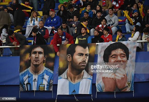 The posters of Argentinian striker Lionel Messi Argentina's midfielder Javier Mascherano and Argentinian football star Diego Maradona are seen before...