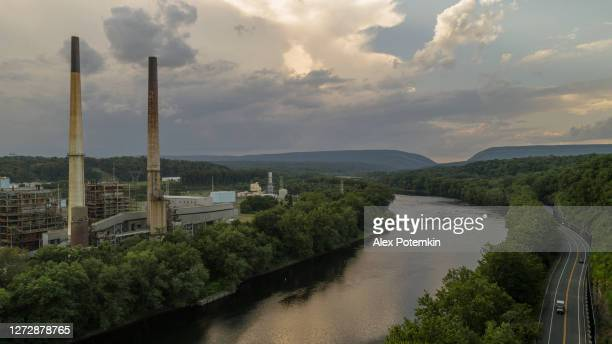 the power plant on the delaware river, at the border between pennsylvania and new jersey, with the remote view on the delaware water gap. an evening with the cloudy dramatic sky and delicate sunlight. - delaware us state stock pictures, royalty-free photos & images