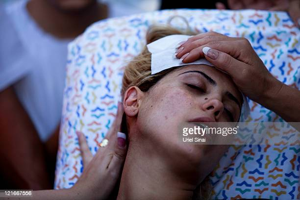 The pregnant wife of Yossi Shooshan is comforted on a stretcher as she mourns her husband's death during his funeral on August 21 2011 in Ofakim...