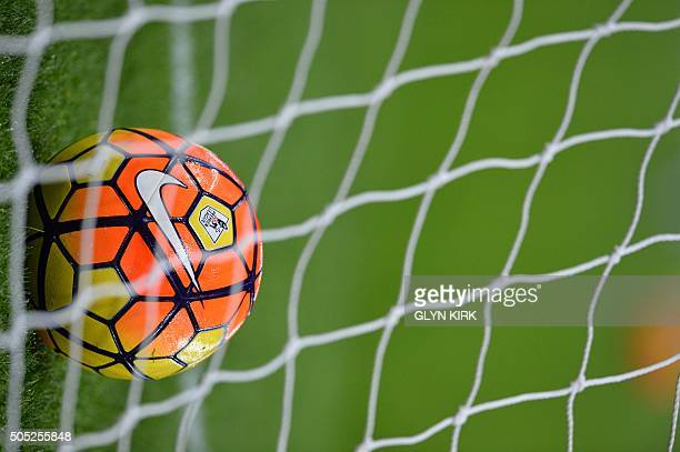 The Premier League and Nike logos are seen on a football behid the net of a goal ahead of the English Premier League football match between Aston...