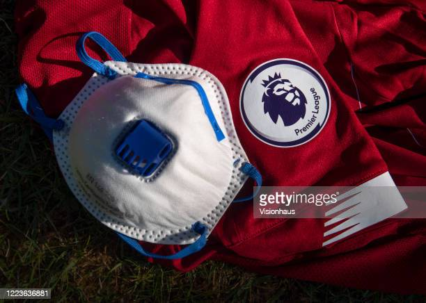 The Premier League logo on the sleeve of a Liverpool shirt with a protective face mask displayed on May 6, 2020 in Manchester, England