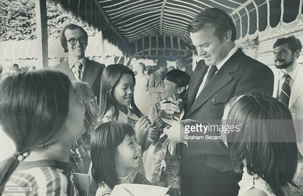 The Premier's Penmanship draws appreciative giggles from a group of little Chinese girls who surrounded Premier William Davis seeking autographs...