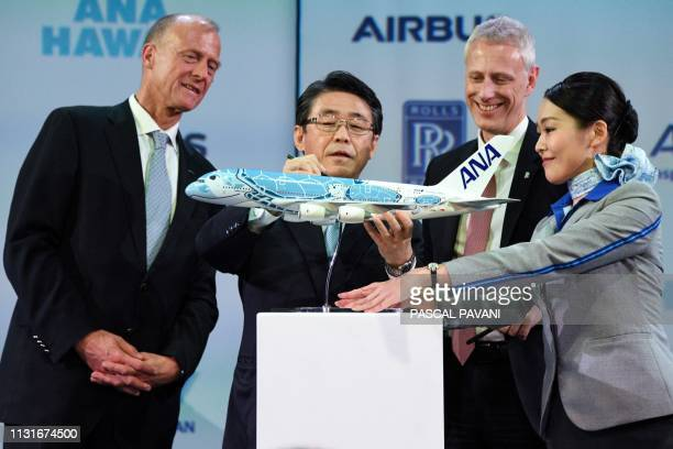 The President and CEO of ANA Holdings Inc Shinya Katanozaka signs an Airbus A380 model flanked by Airbus Chief Executive Officer Tom Enders and Rolls...