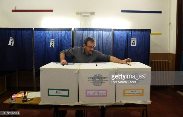 The president of a polling station puts a ballot in the ballot box during the 2018 general election on March 4 2018 in Milan Italy The economy and...