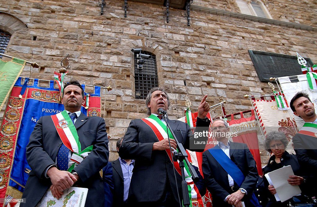The President of ANCI Toscana (National Association of Italian Municipalities) mayor Alessandro Cosimi gives a speech after more than 100 of Central Italy's mayors protest against the Berlusconi Government with a Flash Mob in the Piazza della Signoria on May 20, 2010 in Florence, Italy. Mayors of Central Italy have declared a major emergency of Commons because of the cuts and the rigidity of the Stability Pact asking the Government to loosen budget constraints. The mayors wearing tricolor sashes marched through the streets of Florence and then lay on banners reading ' Thay are knocking your municipality to the ground'