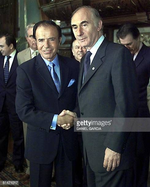 The President of Argentina Fernando de la Rua poses for photographers with former president Carlos Menem 22 September 2000 in the president's private...