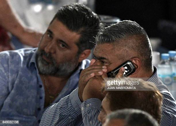 The president of Argentinian football team Barracas Central Claudio Tapia speaks on his mobile phone next to Boca Juniors' president Daniel Angelici...