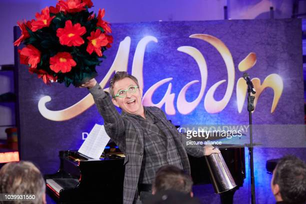 The president of Disney Theatrical Group Tom Schumacher holds a bouquet of flowers during rehearsal for the musical 'Aladdin' at the Stage Theater...
