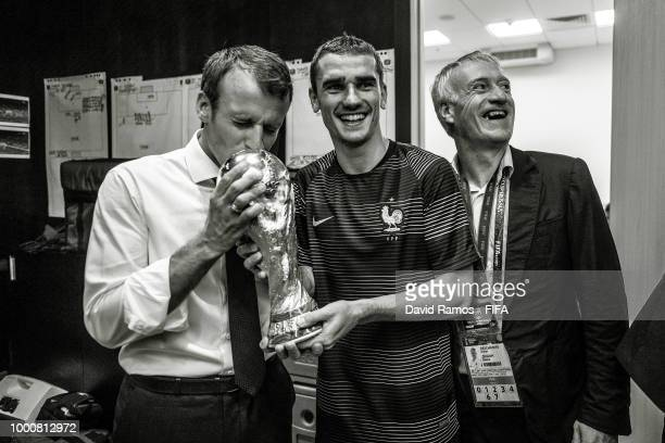 The President of France Emmanuel Macron kisses the World Cup Trophy in the dressing room next to Antoine Griezmann of France and Didier Deschamps...