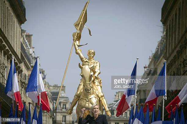 The president of French farright party Front National Marine Le Pen speaks in front of a statue of Joan of Arc during the party's annual celebration...