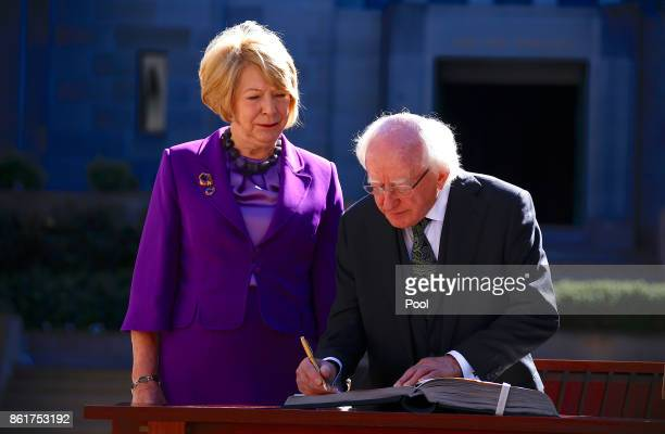 The President of Ireland Michael Higgins is watched by his wife Sabina as he signs the official visitor's book at the Australian War Memorial in...