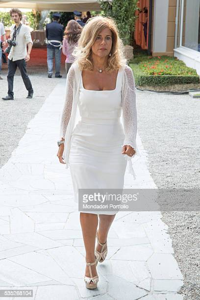 The president of Italian National Hydrocarbon Corporation Emma Marcegaglia wearing a white pencil dress by Dolce e Gabbana with sandals by Esposito...
