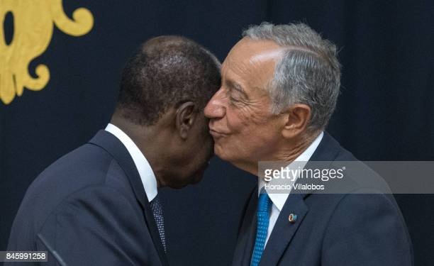 The President of Ivory Coast Alassane Dramane Ouattara embraces with Portuguese President Marcelo Rebelo de Sousa during the press conference at the...
