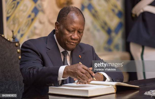 The President of Ivory Coast Alassane Dramane Ouattara signs the honors book in Belem Palace on September 12 2017 in Lisbon Portugal The President of...