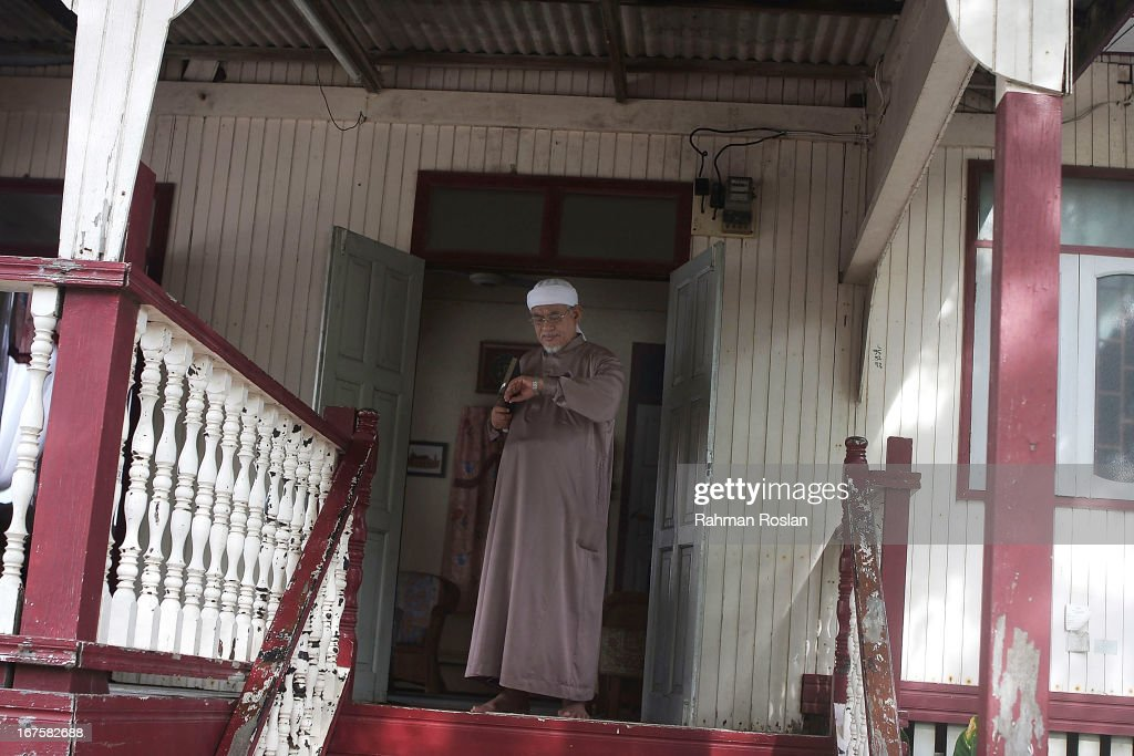 The president of Malaysian Pan Islamic Party, Abdul Hadi Awang checks his watch as he exits his house to deliver his weekly Friday sermon to his followers and students on April 26, 2013 in Rusila, Malaysia. Malaysia's 13th general election will be held on May 5.