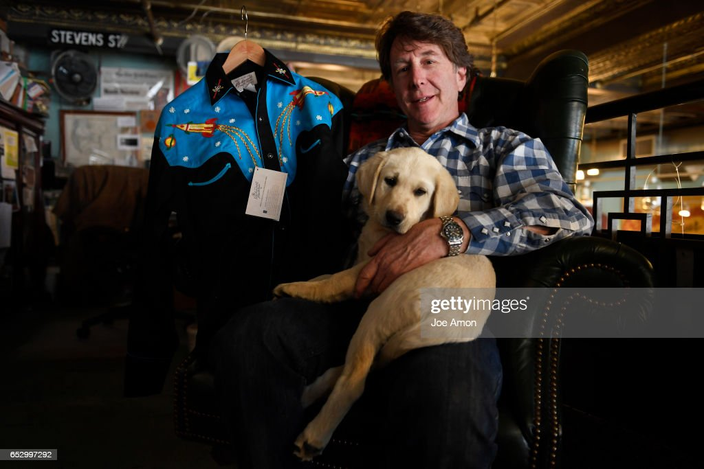 The president of Rockmount Ranch Wear, Steve Weil with his new puppy Humboldt, and the 'Rocket shirt' he feels is being copied by the Coach, Inc