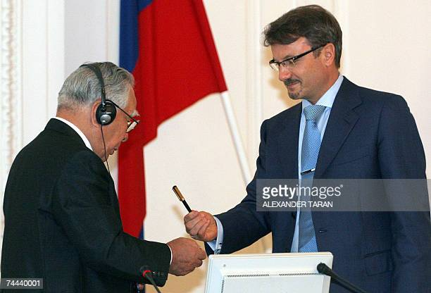 The president of Suzuki Motor Corporation Osamu Suzuki and Russian Minister for Economic Development and Trade German Gref exchange pens during a...