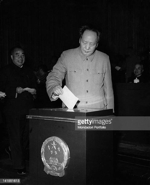 The President of the Chinese Communist Party and President of the People's Republic of China Mao Zedong placing a voting paper inside a ballot box...