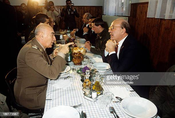 The President of the Council of Ministers of the Italian Republic Bettino Craxi sitting at the table and talking to the Chief of Staff of the Italian...