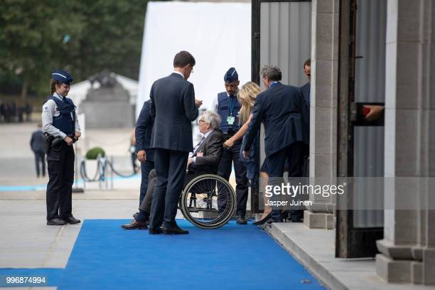 The President of the European Commission JeanClaude Juncker is seen seated in a wheelchair as he is brought in through a side entrance of the...