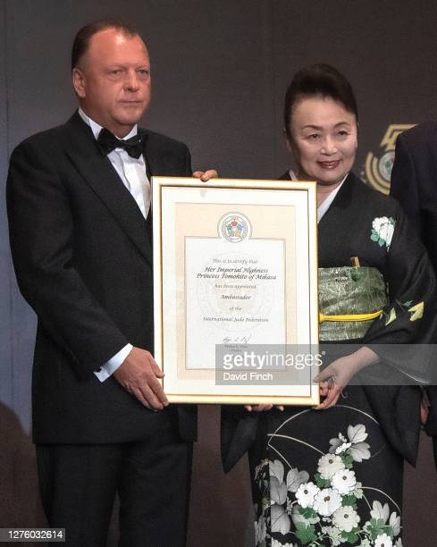 The President of the International Judo Federation, Marius Vizer hands a certificate to Princess Tomohito of Mikasa certifying that she has been...