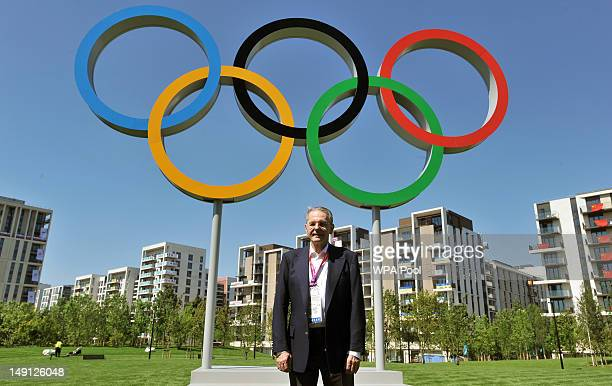 The President of the International Olympic Committee Jacques Rogge stands under the Olympic rings in the Olympic Village during his walk-about before...