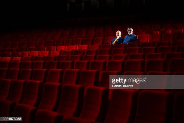 The president of the Karlovy Vary International Film Festival Jiri Bartoska and entertainer Marek Eben sit in the empty movie theater during the...