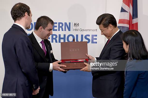 The President of the People's Republic of China Xi Jinping presents a gift of paint brushes and an ink painting made using Graphine ink to Professor...
