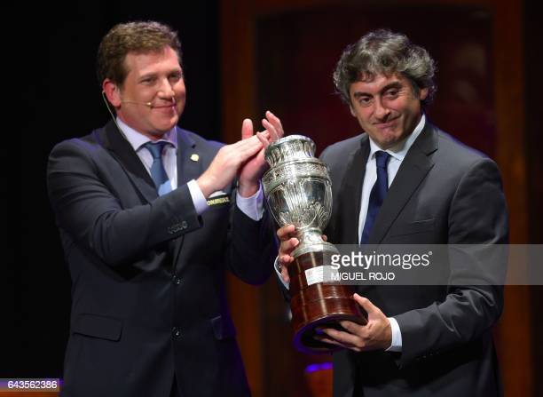 The president of the South American Football Confederation Paraguay's Alejandro Dominguez gives a commemorative trophy to Uruguay's former football...