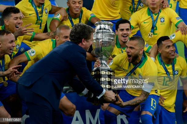 The president of the South American football's governing body Conmebol, Paraguayan Alejandro Dominguez gives the trophy to Brazil's Dani Alves after...